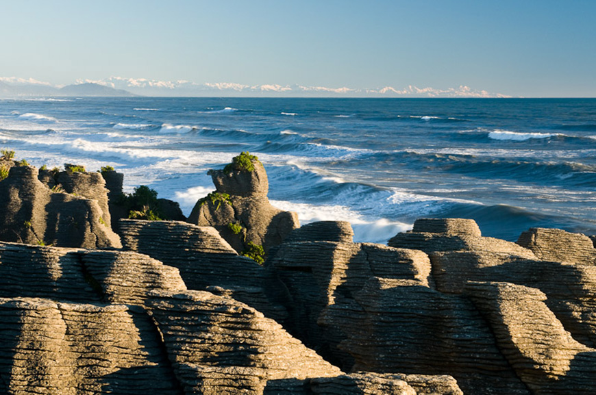 Limestone formations - Pancake Rocks - in Punakaiki, Paparoa National Park. Southern Alps with Mt.Cook visible in a far distance in the top right.